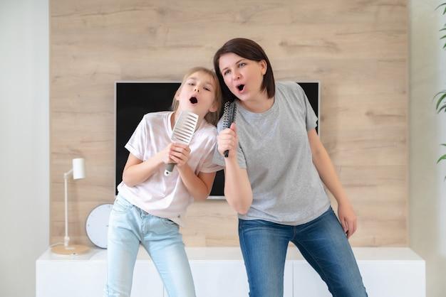 Gelukkige familie jonge volwassen moeder en schattige tiener dochter plezier zingen karaoke lied in haarborstels. moeder lachen genieten van grappige levensstijl activiteit met tienermeisje thuis samen. Premium Foto