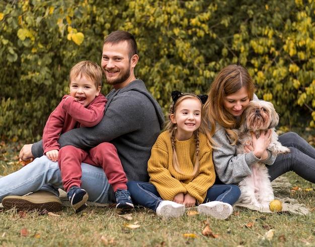Gelukkige familie met hond buiten Gratis Foto
