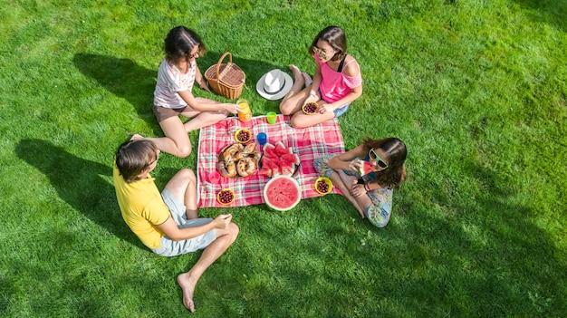 Gelukkige familie met kinderen met picknick in het park, ouders met kinderen zittend op tuingras en gezonde maaltijden buitenshuis eten, luchtfoto drone weergave van bovenaf, familievakantie en weekend concept Premium Foto