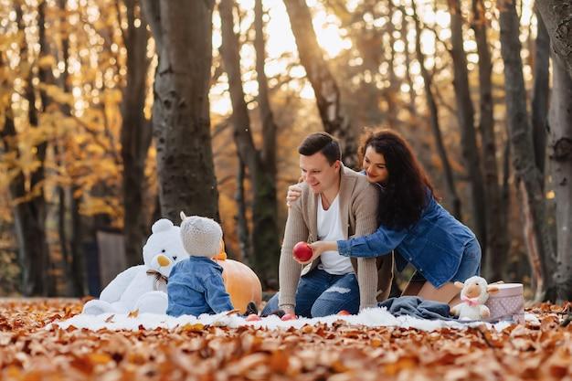 Gelukkige familie met klein schattig kind in park op geel blad met grote pompoen in de herfst Premium Foto