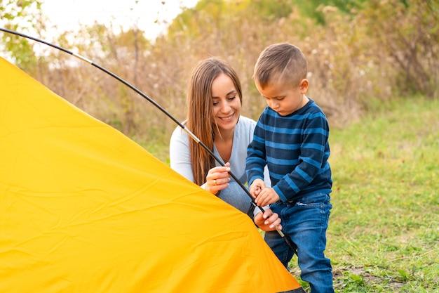 Gelukkige familie met zoontje opgezet camping tent. gelukkige jeugd, kampeertrip met ouders. een kind helpt een tent op te zetten Premium Foto