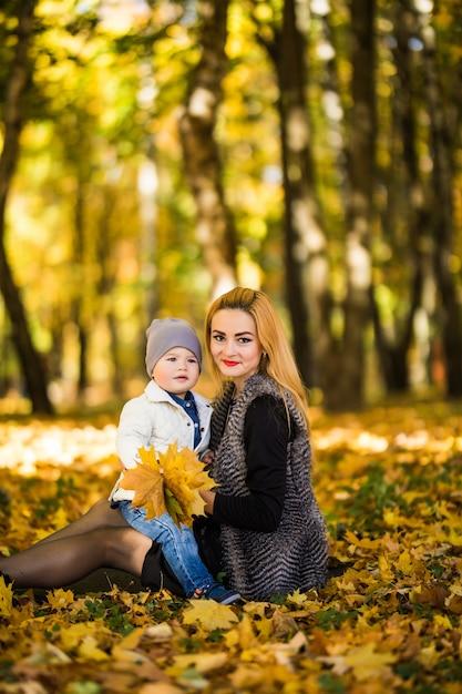 Gelukkige familie moeder spelen met kind in herfst park in de buurt van boom liggend op gele bladeren. herfst concept. Gratis Foto