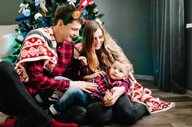Gelukkige familie moeder, vader en zoon in de buurt van de kerstboom met geschenken en open haard. Premium Foto