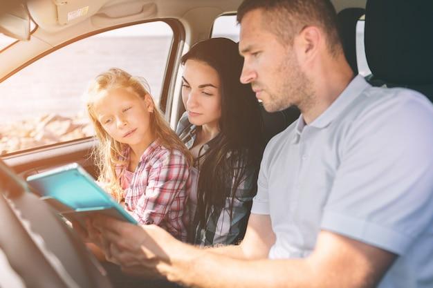 Gelukkige familie op een road trip in hun auto. vader, moeder en dochter reizen langs de zee of de oceaan of de rivier. zomerrit met de auto Premium Foto