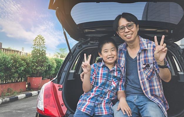 Gelukkige familie op een wegreis, die in boomstam van auto zit Premium Foto