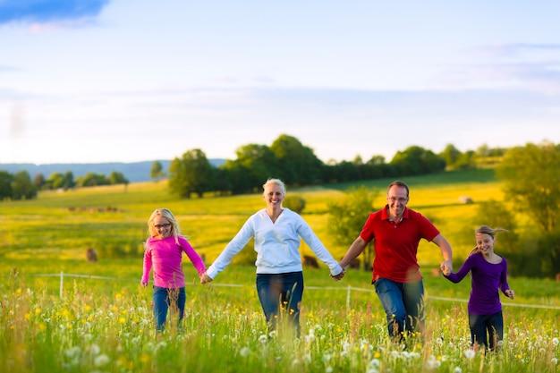Gelukkige familie op weide bij zonsondergang Premium Foto