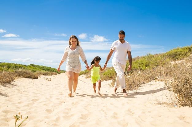 Gelukkige familie paar en klein kind in zomer kleren wandelen wit langs zandpad, meisje hand in hand van de ouders Gratis Foto