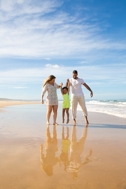 Gelukkige familie paar en meisje genieten van wandelen en activiteiten op het strand, kind hand in hand van de ouders, springen en hangen Gratis Foto