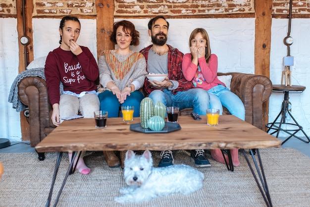 Gelukkige familie thuis films kijken in de bank en het eten van popcorn Premium Foto
