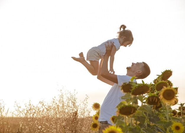 Gelukkige familie, vader en dochter spelen in het veld Gratis Foto
