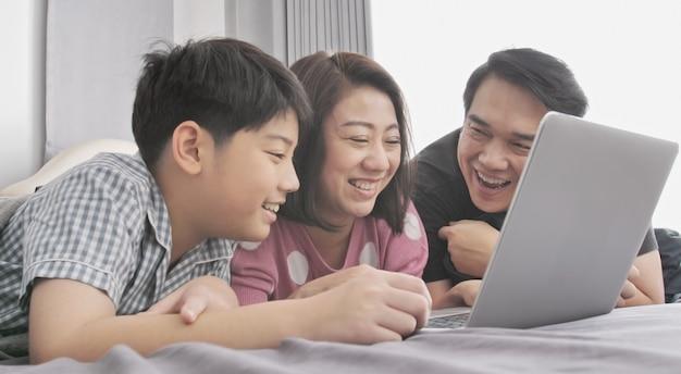 Gelukkige familie vader moeder en zoon kijken op laptopcomputer. Premium Foto