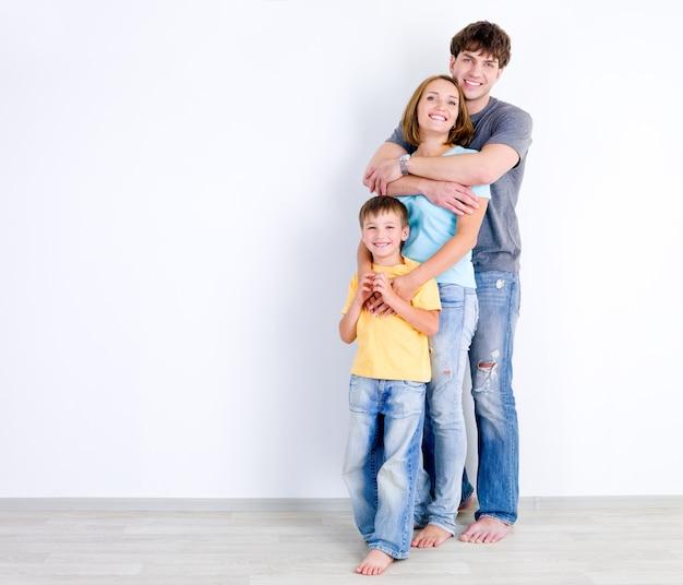 Gelukkige familie van drie mensen die zich in omhelzing dichtbij de lege muur bevinden Gratis Foto