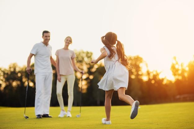 Gelukkige familie van golfspelers op een groene weide. Premium Foto