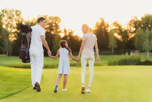 Gelukkige familie verlaat de golfbaan na spel. Premium Foto