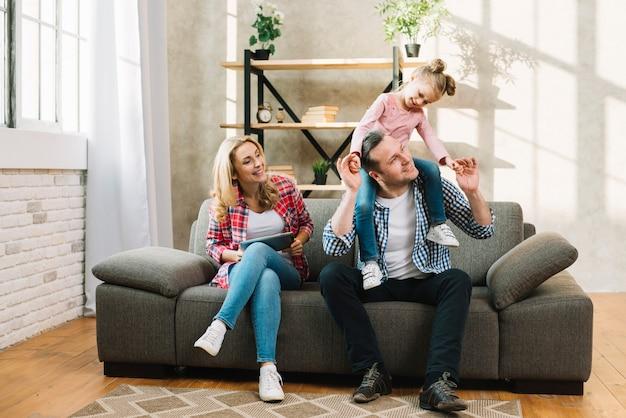 Gelukkige familie zittend op de bank in de woonkamer Gratis Foto