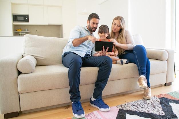 Gelukkige familie zittend op de bank, met behulp van online app op tablet, scherm kijken, samen film kijken. Gratis Foto
