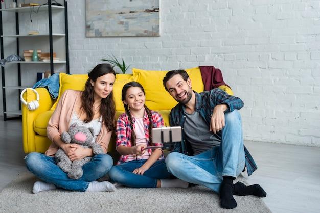 Gelukkige familie zittend op de vloer Gratis Foto