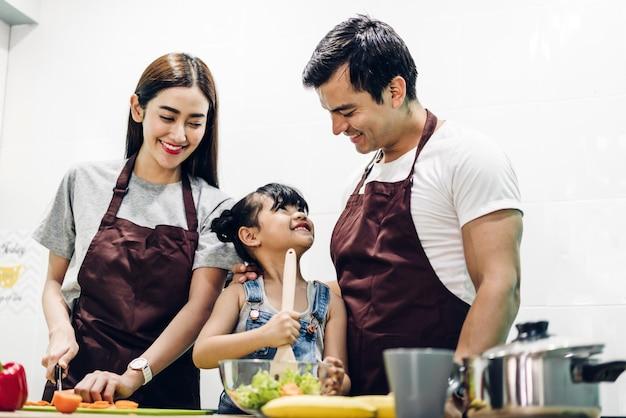 Gelukkige familievader en moeder met dochter die en maaltijd samen in de keuken koken voorbereiden Premium Foto