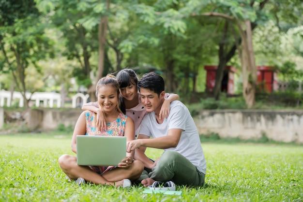 Gelukkige familievader, moeder en dochterzitting op het gras en het spelen van laptop bij openluchtpark Gratis Foto