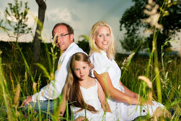 Gelukkige familiezitting in weide Premium Foto