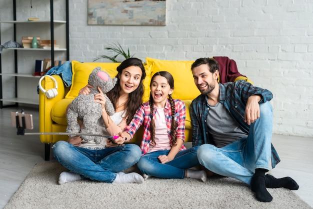 Gelukkige familiezitting op een vloer die een selfie nemen Gratis Foto
