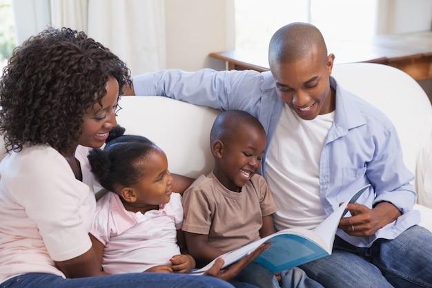 Gelukkige familiezitting op laag die samen boek lezen Premium Foto