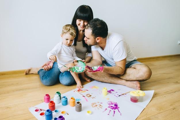 Gelukkige familiezoon met ouders en een kat die een affiche en een andere met verven schilderen Premium Foto