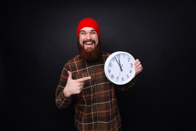 Gelukkige gebaarde mens die een bic witte klok houden en op zwarte achtergrond glimlachen. Premium Foto