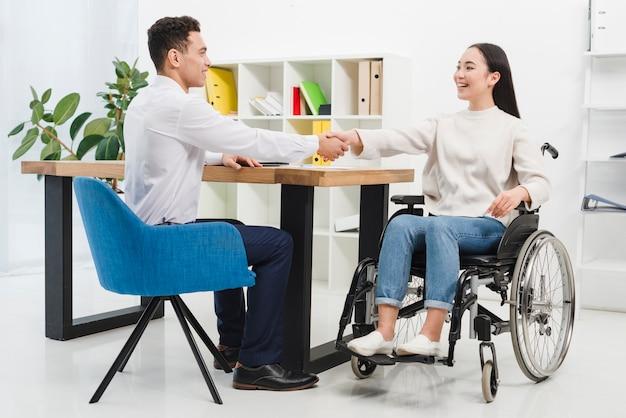 Gelukkige gehandicapte jonge vrouwenzitting op rolstoel het schudden handen met mannelijke collega in het bureau Gratis Foto
