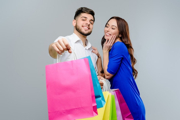 Gelukkige geïsoleerde paarman en vrouw met het winkelen zakken Premium Foto