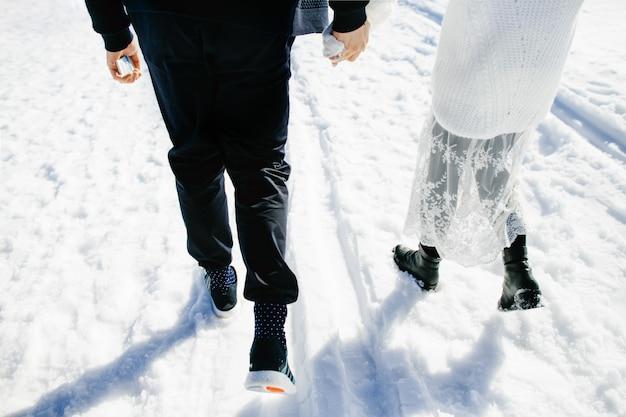 Gelukkige geliefden lopen samen in de sneeuw Gratis Foto