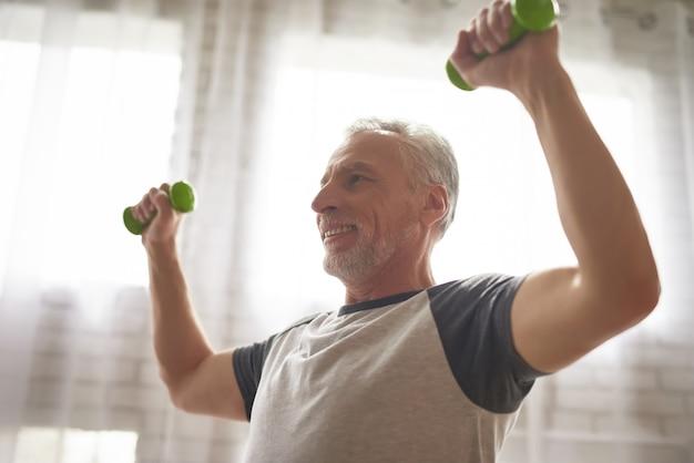 Gelukkige gepensioneerde doet halters oefeningen thuis. Premium Foto