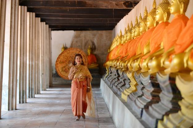 Gelukkige gepensioneerde vrouw in de traditionele thaise jurk reizen in de tempel. Gratis Foto