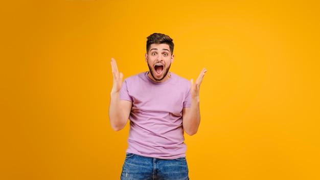 Gelukkige gillende jonge die mens over gele achtergrond wordt geïsoleerd Premium Foto