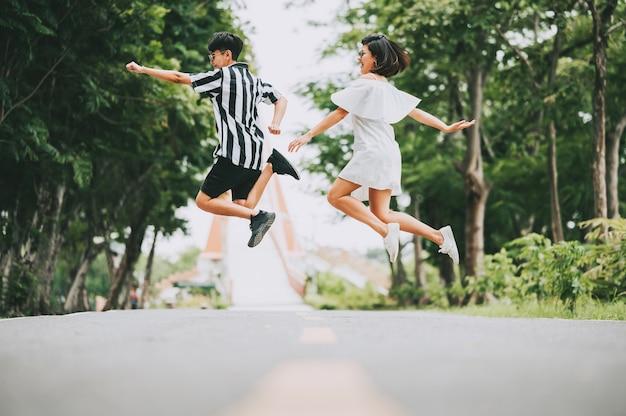Gelukkige glimlach aziatisch lesbisch paar dat van de grond buiten in het park springt. Premium Foto