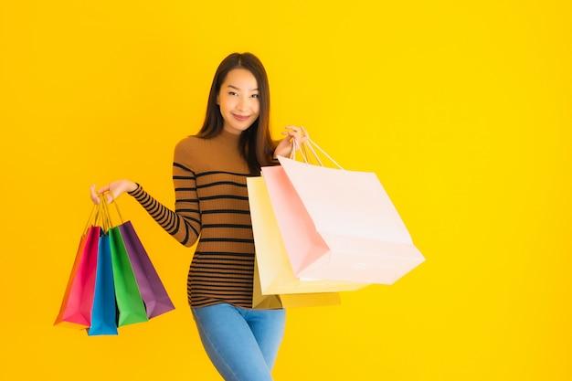 Gelukkige glimlach van de portret de mooie jonge aziatische vrouw met heel wat kleuren het winkelen zak van warenhuis op gele muur Gratis Foto