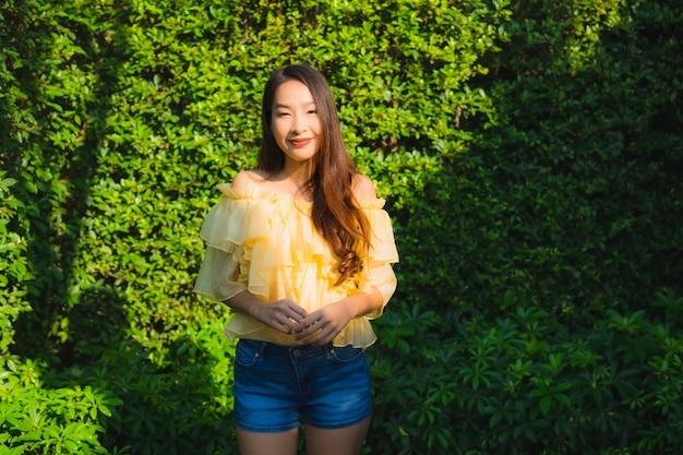 Gelukkige glimlach van de portret ontspant de jonge aziatische vrouw rond openluchtaardtuin Gratis Foto