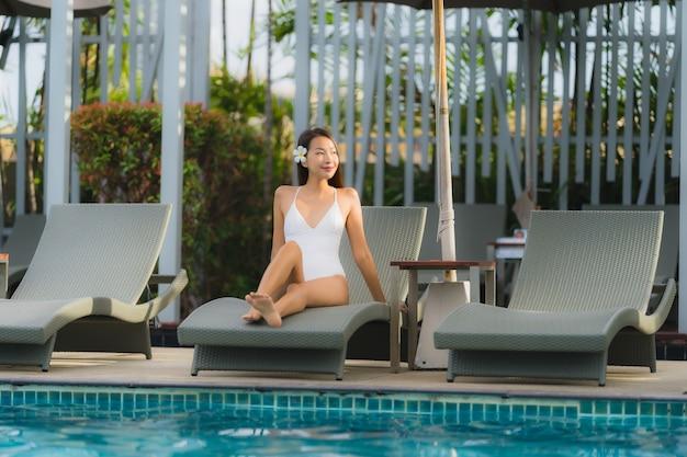 Gelukkige glimlach van de portret ontspant de jonge aziatische vrouw rond zwembad in hoteltoevlucht Gratis Foto