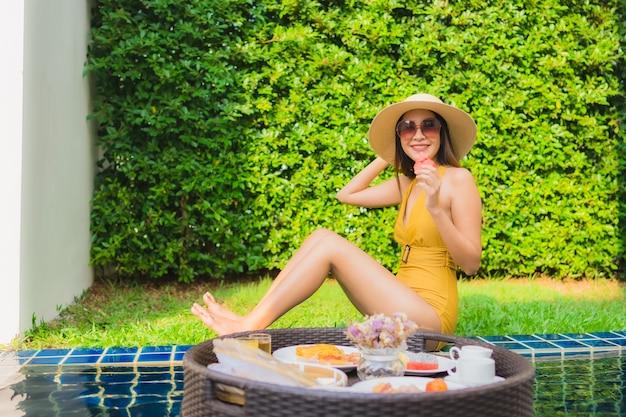 Gelukkige glimlach van de portret ontspant de mooie jonge aziatische vrouw met ontbijt die rond zwembad drijven Gratis Foto