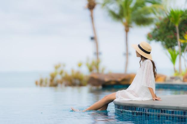 Gelukkige glimlach van de portret ontspant de mooie jonge aziatische vrouw rond zwembad in hoteltoevlucht Gratis Foto