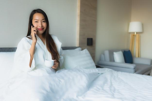 Gelukkige glimlach van portret de mooie jonge aziatische vrouwen met koffie en mobiele telefoon Gratis Foto
