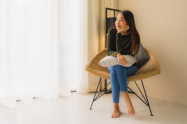 Gelukkige glimlach van portret ontspant de mooie jonge aziatische vrouwen ontspannen zitting op bankstoel Gratis Foto