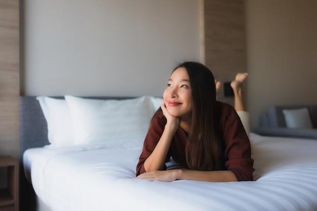 Gelukkige glimlach van portret ontspant de mooie jonge aziatische vrouwen op bed Gratis Foto