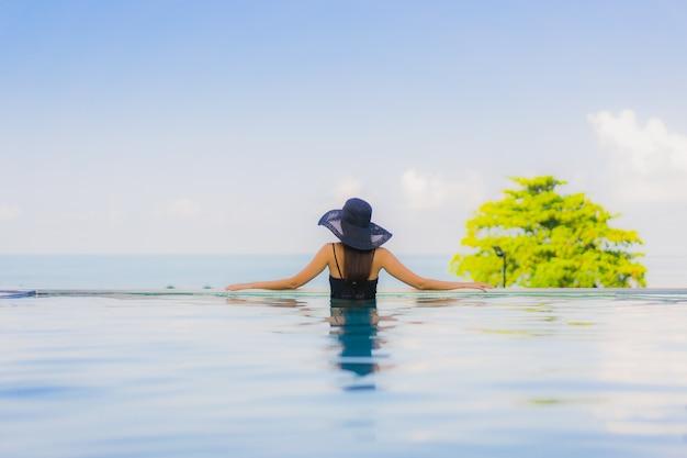 Gelukkige glimlach van portret ontspant de mooie jonge aziatische vrouwen openlucht zwembad in hotel Gratis Foto