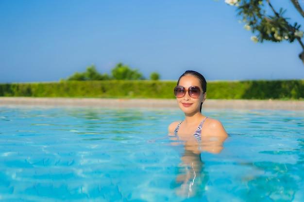 Gelukkige glimlach van portret ontspant de mooie jonge aziatische vrouwen openlucht zwembad in toevlucht Gratis Foto