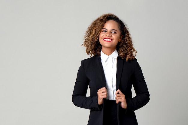 Gelukkige glimlachende afrikaanse amerikaanse vrouw in formele bedrijfskledij Premium Foto