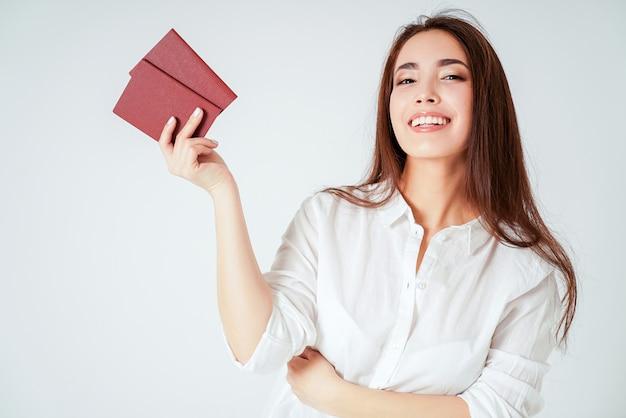 Gelukkige glimlachende aziatische jonge lange haarvrouw met twee paspoorten op witte geïsoleerde achtergrond Premium Foto