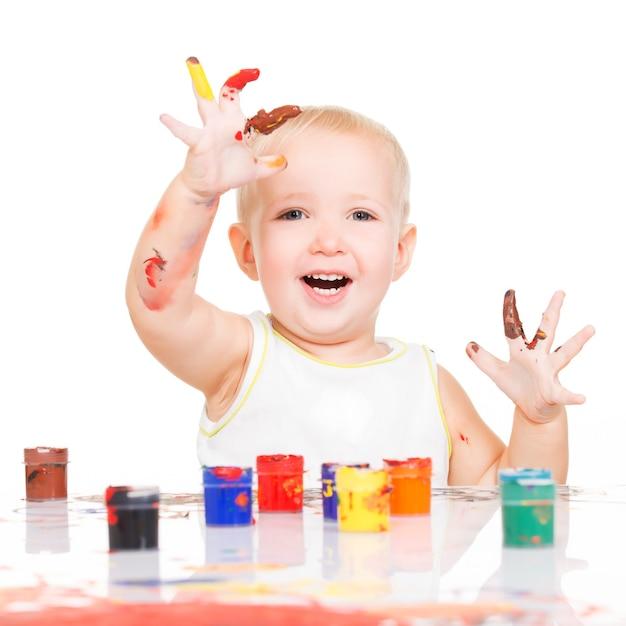 Gelukkige glimlachende baby met geschilderde die handen op wit wordt geïsoleerd. Gratis Foto