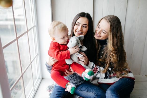 Gelukkige glimlachende familie bij studio op achtergrond van de kerstboom met gift Gratis Foto