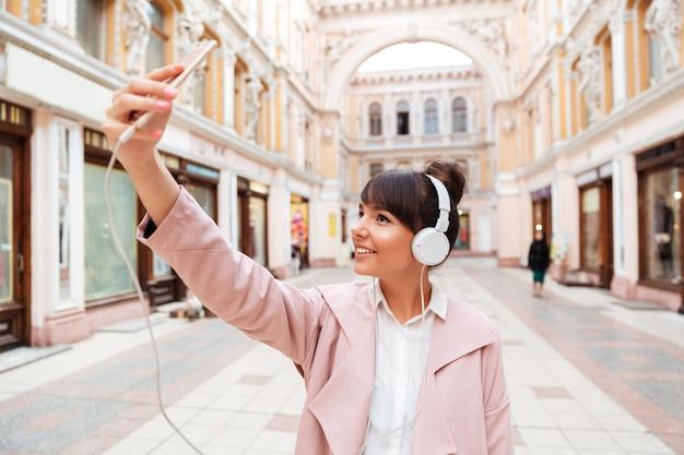 Gelukkige glimlachende jonge vrouw die in hoofdtelefoons selfie foto maken Gratis Foto